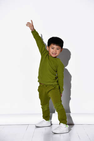 Fashion portrait of a cute little boy in a stylish green tracksuit against a white studio wall background. The boy raises his hands up - hurray, win Stockfoto