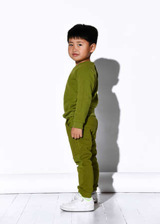 Fashion portrait of a cute little boy in stylish green tracksuit against white studio wall background. Baby fashion concept
