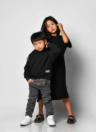 Portrait of two beautiful Asian children posing in front of the camera in the studio against a white background. A cool boy in a black hoodie and jeans with an older sister in a black dress is fun.