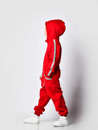 Boy wearing red warm jumpsuit and hood, white snickers shoes posing by side for camera over studio wall background. Full length portrait. Junior fashion, casual clothes for children Stockfoto