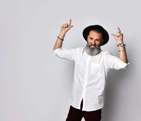 Portrait of a cheerful middle-aged man in a fashionable black hat standing on a gray background and showing the peace sign, hands lifted up happily. Street style. Stylish seniors concept.