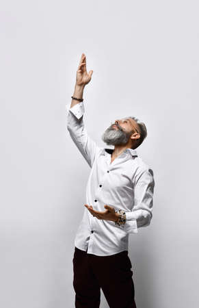 Side view of a stylish pensive bearded man looking up with his hand raised.