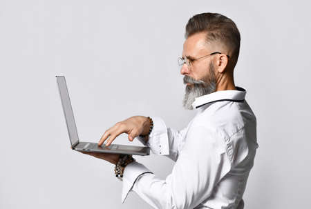 Studio portrait of a middle aged hipster man holding a laptop and looking at the camera. Zdjęcie Seryjne