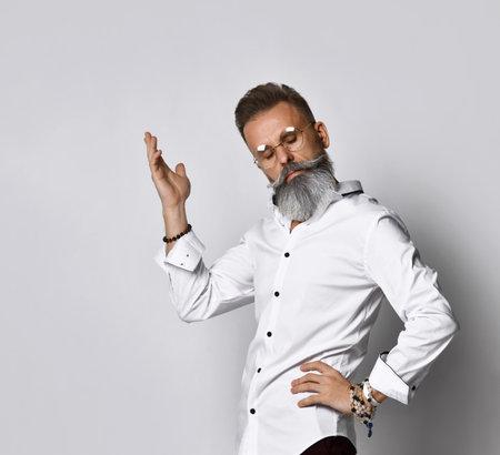 Confused stylish bearded hipster man in eyewear raising hand