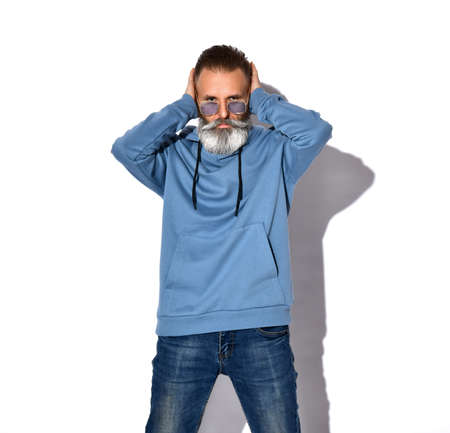 Bearded man in sunglasses, sweatshirt covering ears with palms