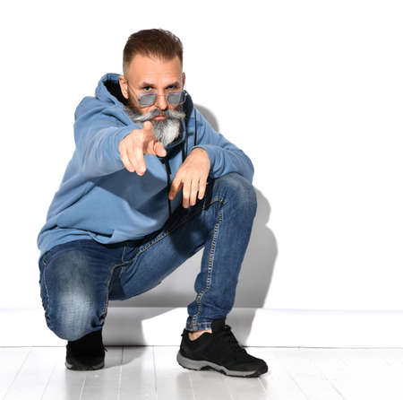 Mature bearded man squatting pointing finger to camera