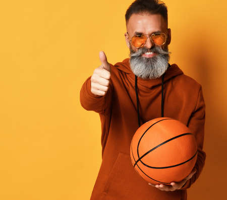 Smiling bearded man holding basket ball gesturing thumbs-up
