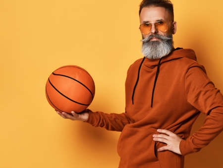 Serious bearded man in sunglasses, hoodie holding basket ball