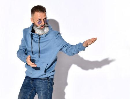 Mature bearded man squatting pointing finger to side Zdjęcie Seryjne