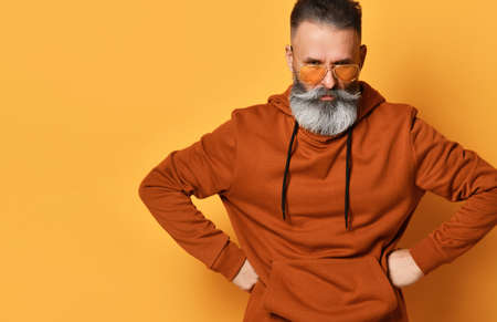 Frowning menacing bearded man in sportswear with hands on hips