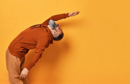 Strong bearded man bending backwards studio shot