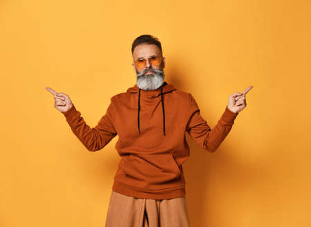 strict elderly handsome man with a beard wearing fashionable glasses and a sweatshirt with a hood, pointing with his index fingers to the sides on a yellow background.