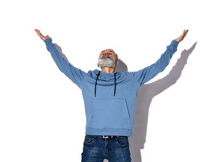 Stylish bearded hipster man with hallelujah gesture looking upward