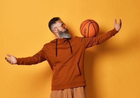 Bearded man showing trick with basket ball studio shot Zdjęcie Seryjne