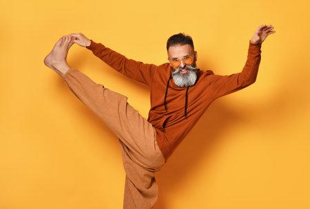 Barefoot funny bearded man in sportswear doing leg stretching