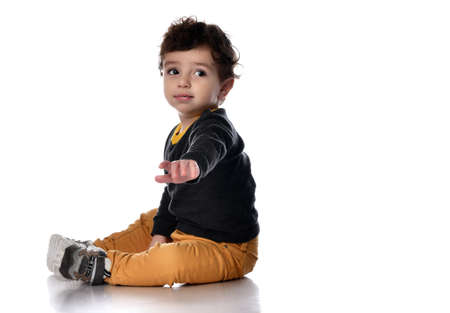 Little boy sits sideways on a white background and reaches for the camera looking to the side.