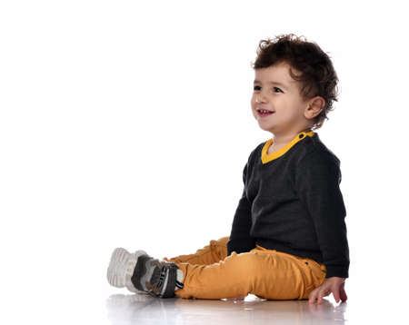 Side view of a handsome stylish baby boy sitting on white background and smiling.