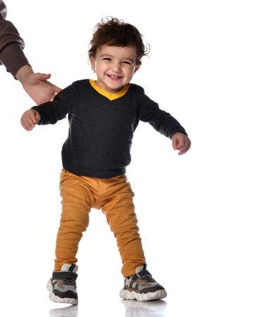 Happy little kid boy learning to walk standing on two legs against white background in studio. Zdjęcie Seryjne