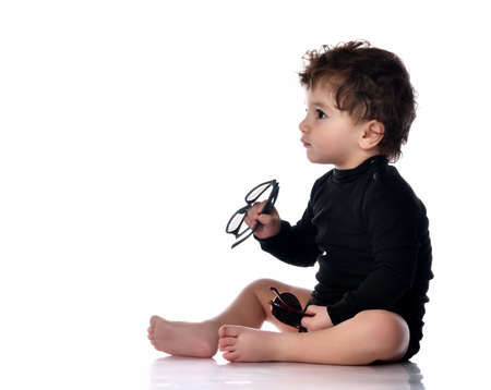 Baby holding glasses taking first step portrait isolated on white