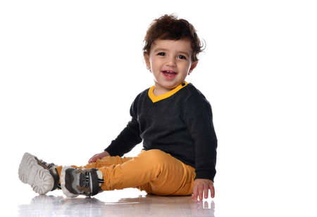 Infant boy in yellow pants sits sideways on the floor looking at us against a white background with space for free text