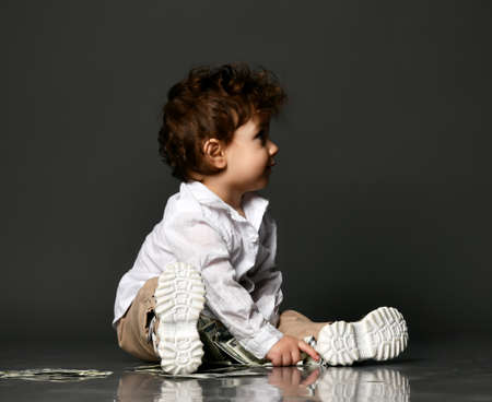 Fashion baby playing with paper money isolated shot