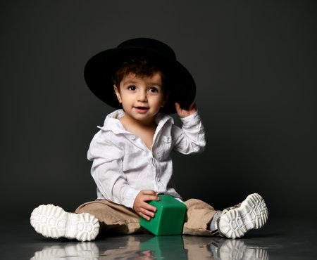Stylish fashion baby boy in hat portrait isolated on gray