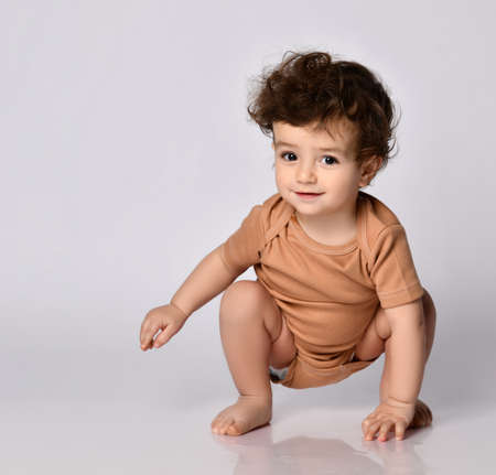 Charming dark-haired curly baby boy crawls on all fours on a gray background.