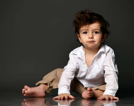 Serious stylish baby sitting on floor looking at camera portrait