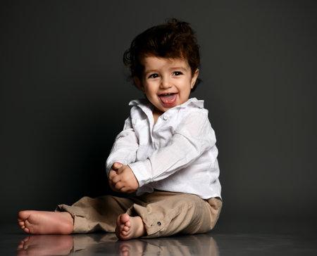 Funny stylish baby showing tongue portrait isolated on gray Zdjęcie Seryjne
