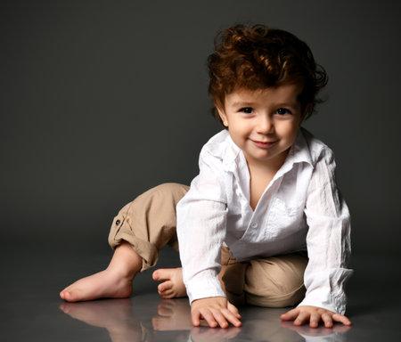 Stylish baby boy smiling slyly, grinning portrait