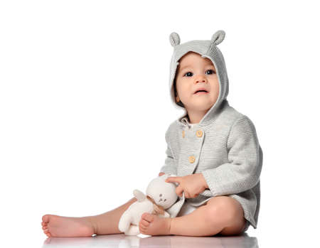 Baby in knitted sweatshirt with hood hugging toy bunny