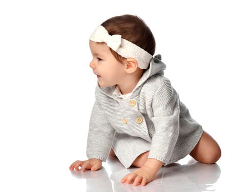 Smiling curious baby in knitted wear on floor