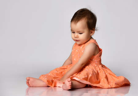 Cute little girl of mixed Caucasian and Asian nationality sits barefoot on a gray background.