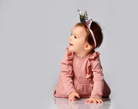 Little cute baby in a crown-shaped headband sits on a gray background. dad and mom princess