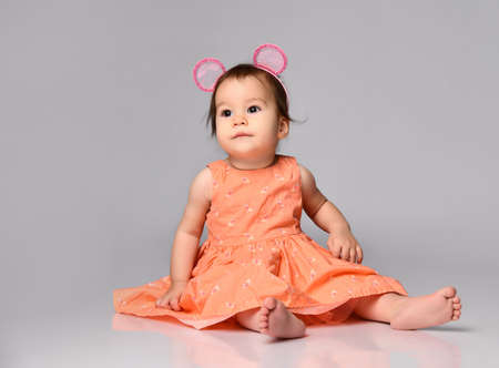 Portrait of a sweet baby girl dressed in a dress and a hoop with ears sitting on gray in the studio.