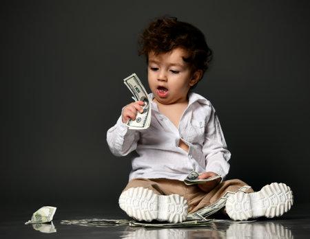 Stylish baby with money portrait isolated on gray Zdjęcie Seryjne