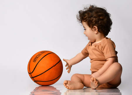 Little boy sitting barefoot and playing a new basketball on a gray background.