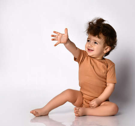Cute little curly boy extends his hand forward sitting barefoot on a gray background.