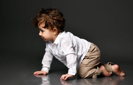 Overjoyed stylish baby crawling portrait isolated on gray Zdjęcie Seryjne