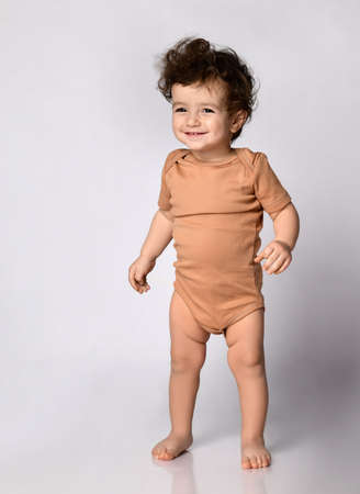 Little baby boy stands on a gray background in the studio and looks at the camera.