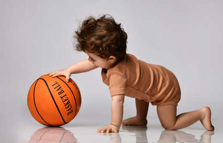 Baby boy dressed in a bodysuit with interest plays a basketball on a gray background.