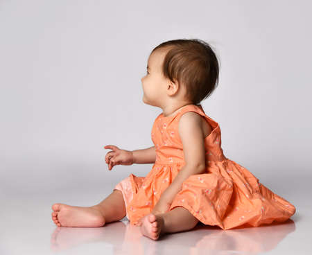 Little girl in a pink dress sits barefoot on a gray background and looks away from the camera.