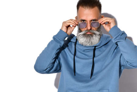 Headshot of serious mature grey-haired bearded man in casual sweatshirt touching trendy sunglasses on face. Fashion and style. Studio portrait isolated on white background with copy space