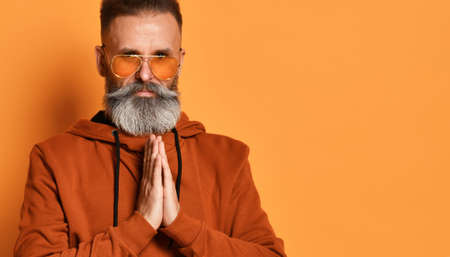 Serious handsome gray-haired bearded hipster in everyday sportswear and sunglasses with folded hands on the chest in prayer, looking into the camera. Studio shot isolated on yellow background