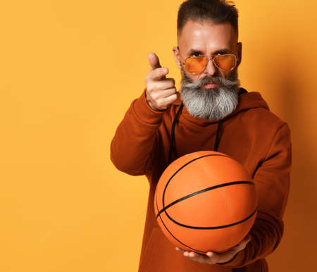 Bearded man offering to practice basketball game studio shot
