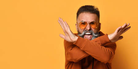 Bearded man in sportswear shouting showing no stop gesture with hands crossed Zdjęcie Seryjne