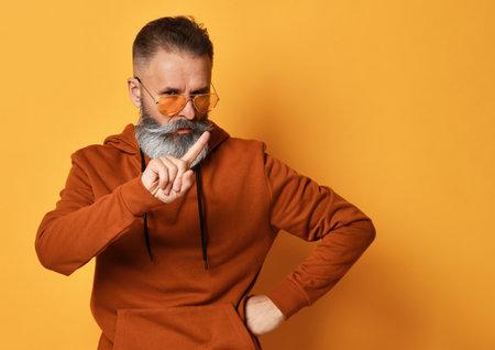 Frowning bearded man in sportswear rejecting offer