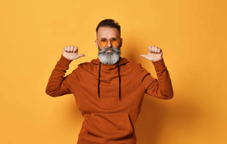 Portrait of smiling old man pointing itself over yellow background
