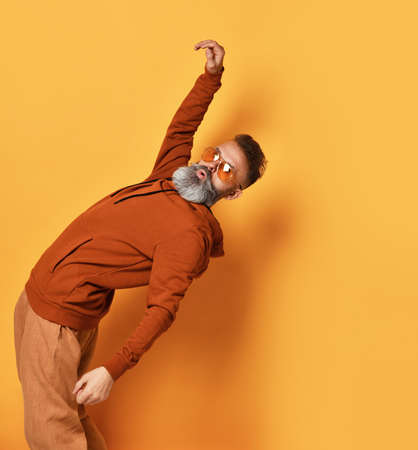 Strong brutal white-haired, bearded man in sportswear and fashion sunglasses, leaning back. Sports fashion, the strength of the people. Studio shot isolated on yellow background with copy space Zdjęcie Seryjne
