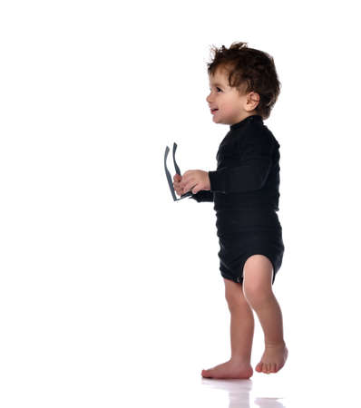 Baby boy holding glasses taking first step. Smart barefoot child learning training to walk. Isolated portrait shot on white studio background. Happy childhood and generation. Kid growth, development Zdjęcie Seryjne